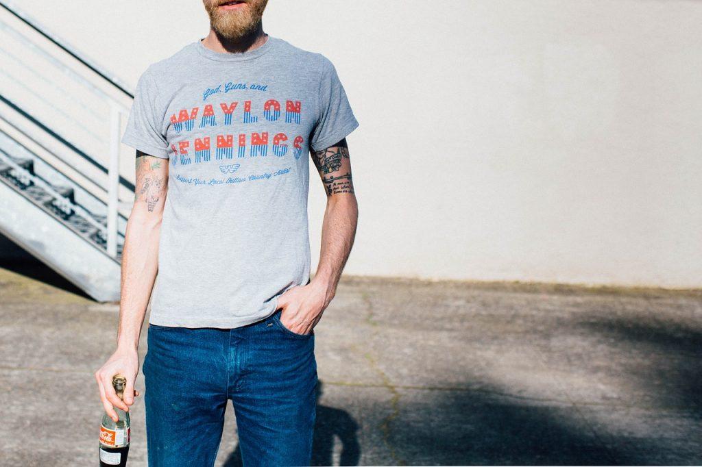 Chico bebiendo una coca cola con su camiseta hipster